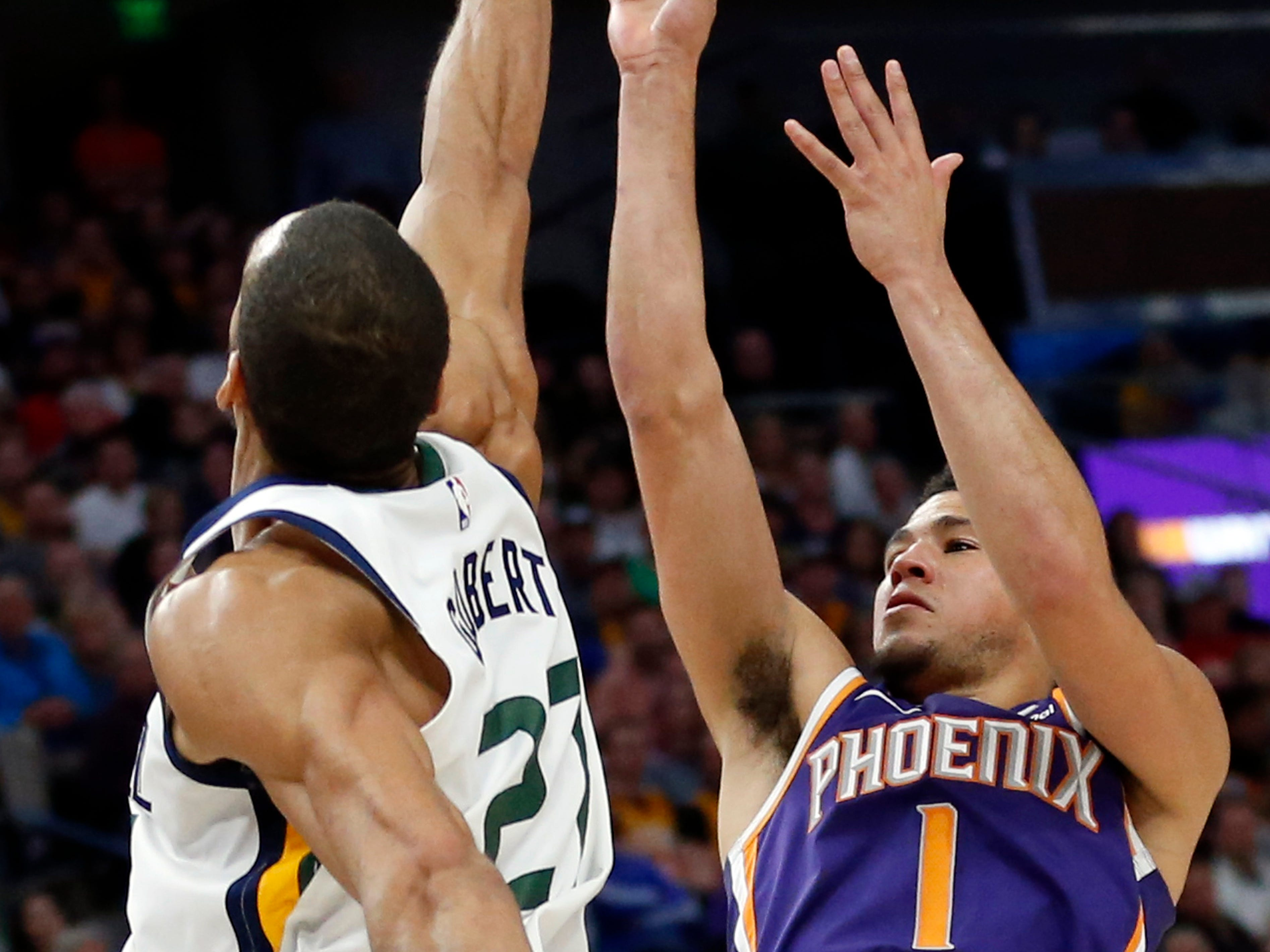 Utah Jazz center Rudy Gobert (27) blocks the shot of Phoenix Suns guard Devin Booker (1) during the first half of an NBA basketball game Monday, March 25, 2019, in Salt Lake City.