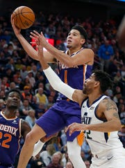 Phoenix Suns guard Devin Booker (1) goes to the basket as Utah Jazz forward Thabo Sefolosha (22) defends during the first half of an NBA basketball game Monday, March 25, 2019, in Salt Lake City. (AP Photo/Rick Bowmer)