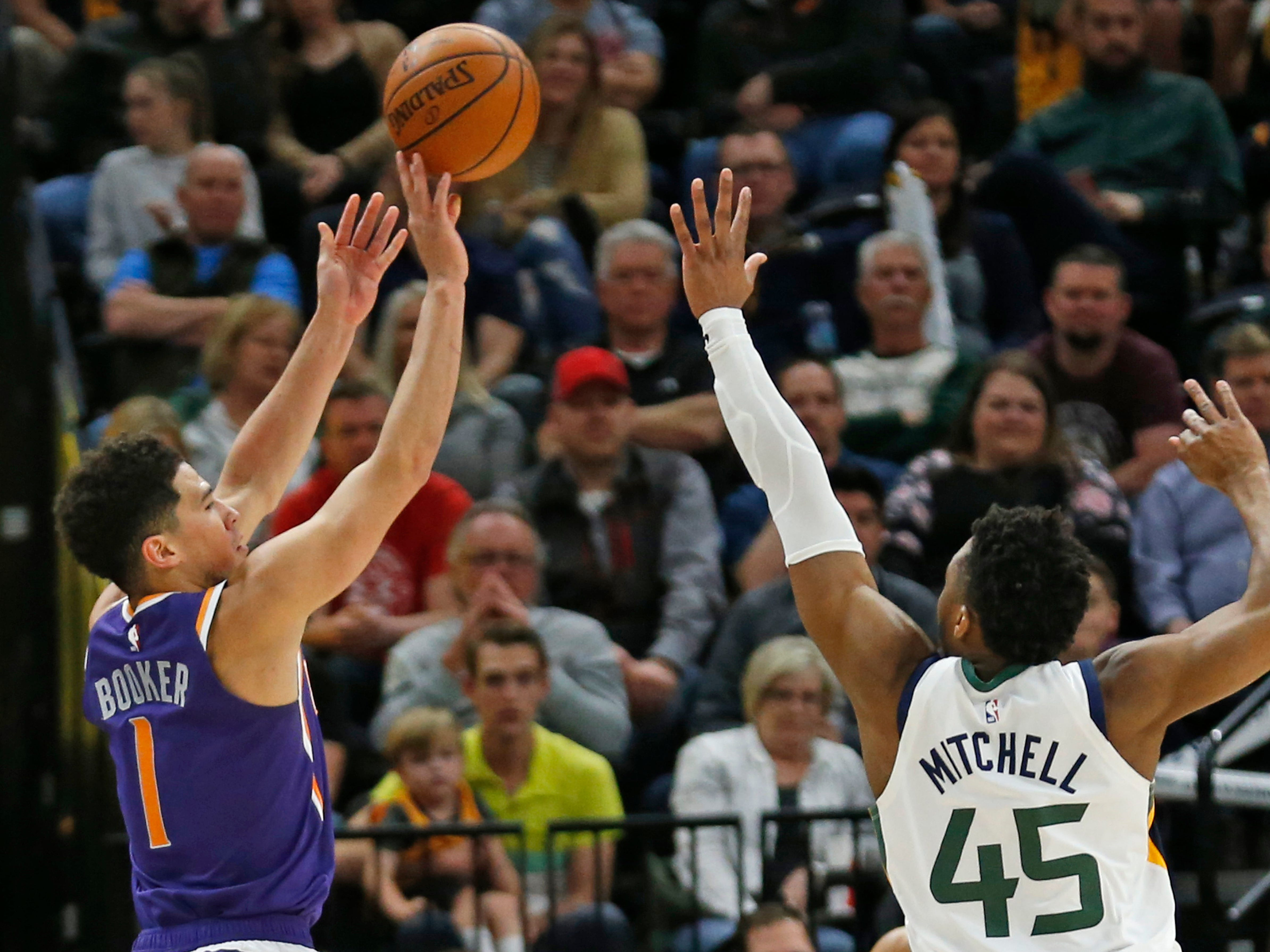 Phoenix Suns guard Devin Booker (1) shoots as Utah Jazz guard Donovan Mitchell (45) defends during the second half of an NBA basketball game Monday, March 25, 2019, in Salt Lake City.