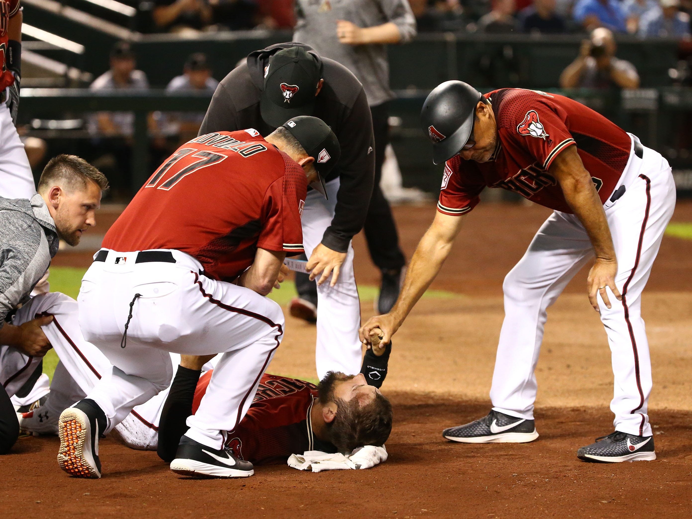 Arizona Diamondbacks coach Tony Perezchica (right) holds the hand of Steven Souza Jr. reacts after suffering an injury to his leg after scoring against the Chicago White Sox in the fourth inning during a spring training game on Mar. 25, 2019 at Chase Field in Phoenix, Ariz. Steven Souza Jr. was carried from the field.