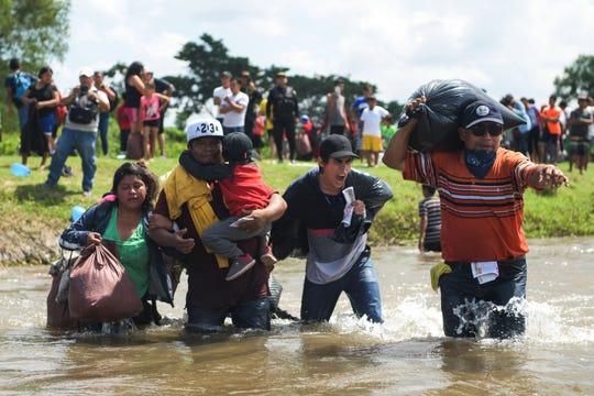 Migrantes salvadoreños cruzan un río.