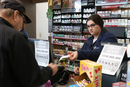 Courtney Whiting hands a Powerball ticket to Dave Benton, of Millbury, at the Friendship Food Store in Port Clinton on Tuesday.
