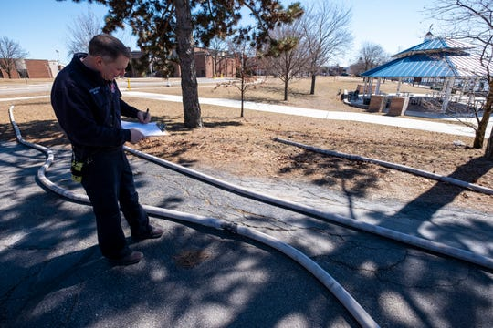 Port Huron Fire Battlion Chief Dale Minard inspects a coupling between two hoses Tuesday, March 26, 2019 outside of Port Huron's central station.