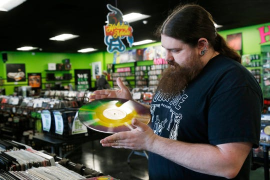 Darkside Records co-owner Justin Johnson looks over a used record at Darkside Records in the Town of Poughkeepsie on March 25, 2019.