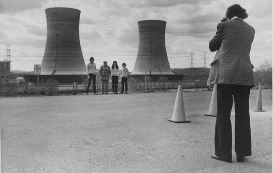A group of tourists have their photograph taken by a family member as they pose with cooling towers from Three Mile Island nuclear power plant near Middletown, Pa., May 11, 1979. (AP Photo/Fred Prouser)