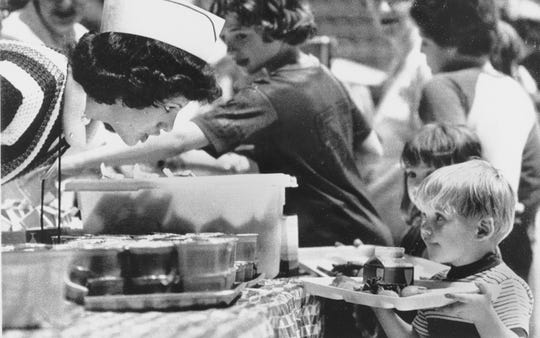 A Red Cross volunteer leans over to make sure a youngster has everything he wants for lunch at the evacuation center in Hershey Park, Pa., April 4, 1979. Expectant mothers and preschool children were asked to remain at the center for those who live within a 5-mile radius of the Three Mile Island nuclear plant. (AP Photo/Rusty Kennedy)