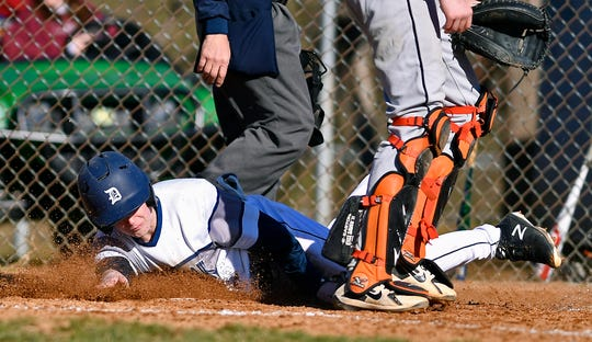 Dallastown's Riley Thomas slides past York Suburban catcher RJ Marquis to score in the second inning, Tuesday, March 26, 2019