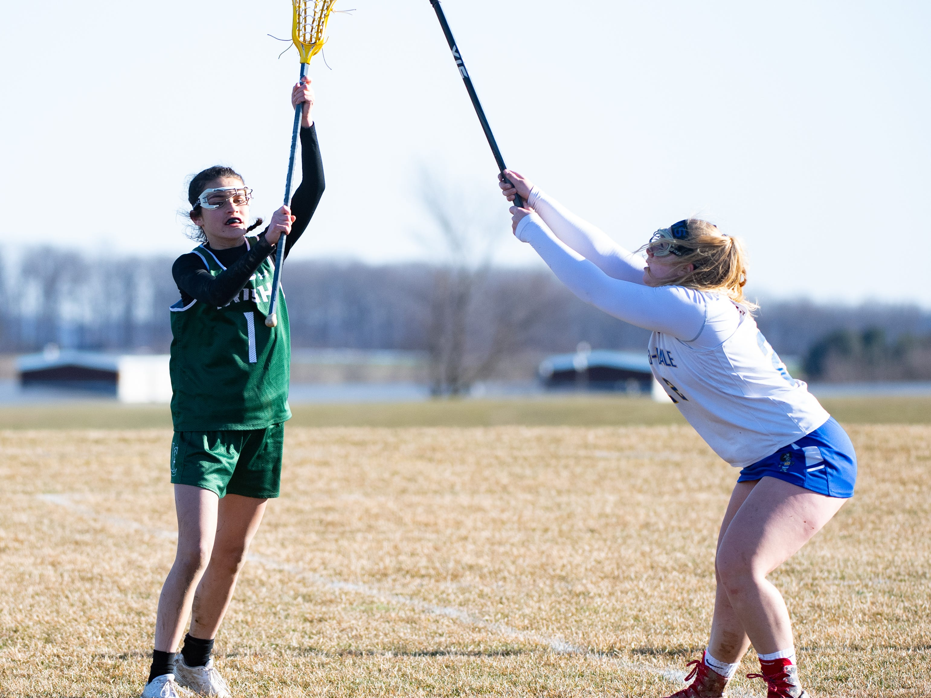 Olivia Staples (1) passes behind the net during the girls' lacrosse game between Kennard-Dale and York Catholic, March 26, 2019 at Kennard-Dale High School. The Fighting Irish defeated the Rams 10 to 9.