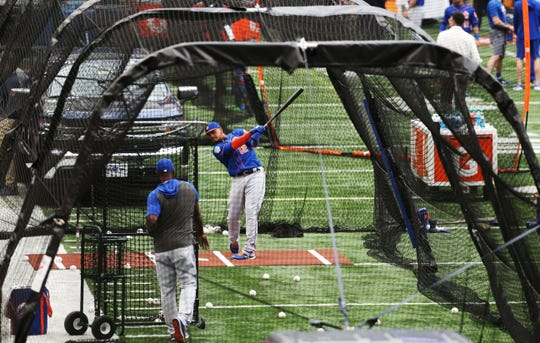 A New York Met takes batting practice at the Carrier Dome at Syracuse University on Tuesday with a coach behind a Valle Shield screen.