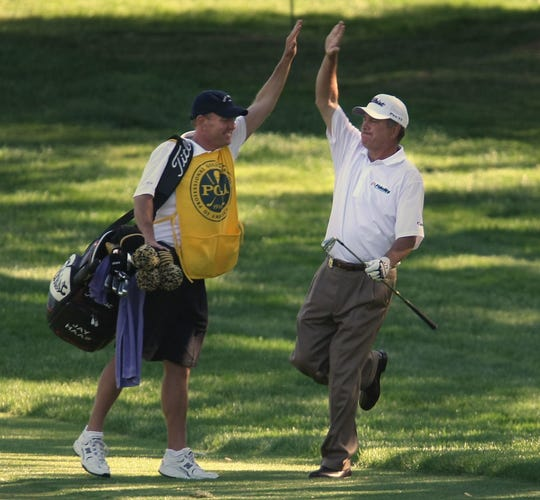 Jay Haas high-fives his caddie after holing out for an eagle on No. 17 at Oak Hill during the third round of the 2008 Senior PGA Championship. Haas won the 2008 Senior PGA Championship by one stroke over Bernhard Langer.