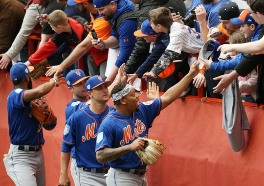 Dominic Smith gives his hat to a fans at the New York Mets' workout at the Carrier Dome at Syracuse University on Tuesday.