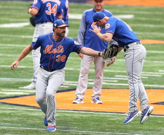 Mickey Callaway tags Jeff McNeil during the team's workout at the Carrier Dome at Syracuse University on Tuesday.