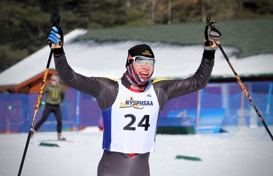 Honeoye Falls-Lima's Teddy Warfle celebrates the Cougars' victory at the New York State Nordic Skiing Championships.