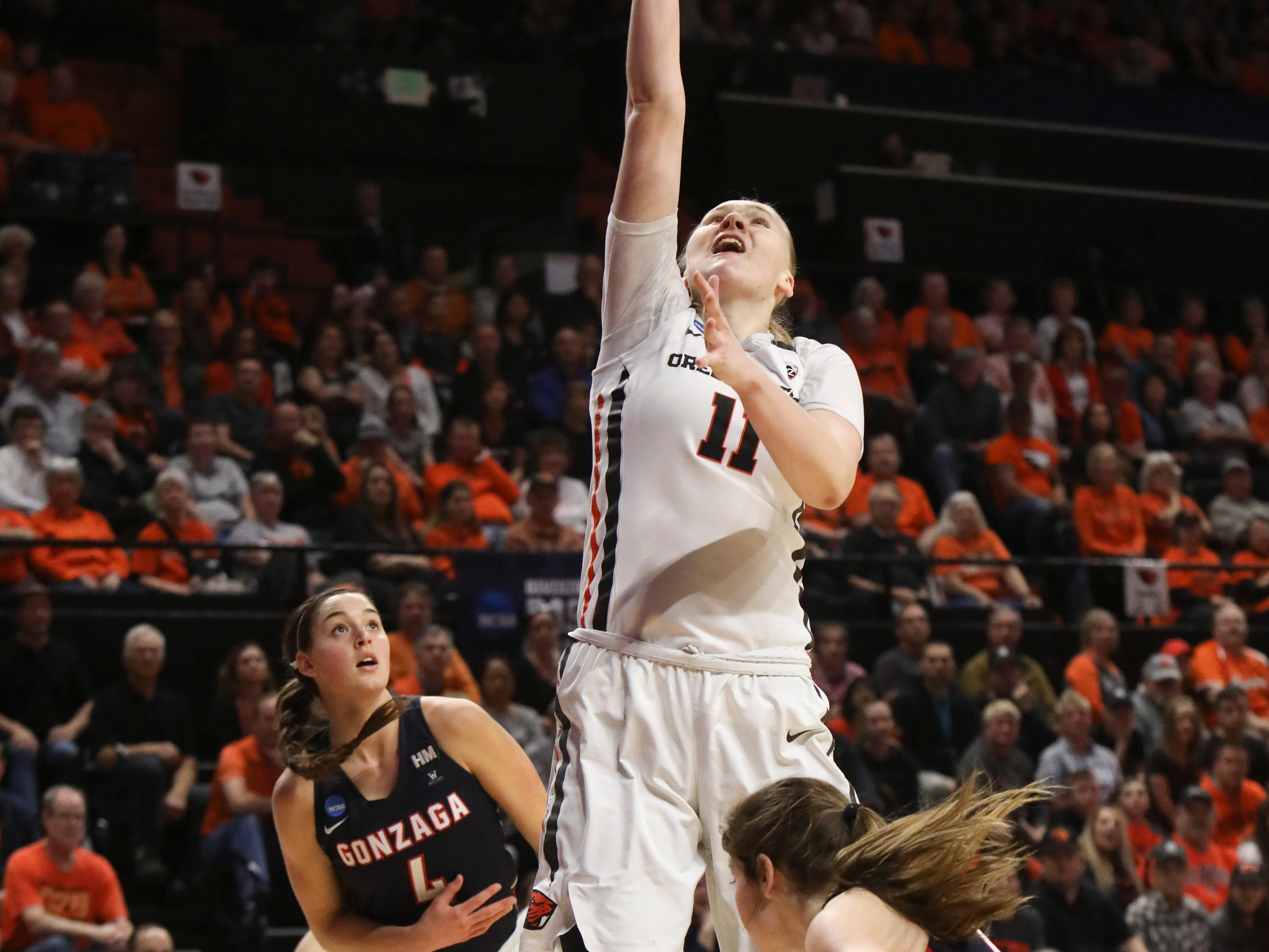Oregon State's Joanna Grymek (11) makes it through Gonzaga's LeeAnne Wirth (4) and Katie Campbell (24) to score during the first half of a second-round game of the NCAA women's college basketball tournament in Corvallis, Ore., Monday, March 25, 2019. (AP Photo/Amanda Loman)
