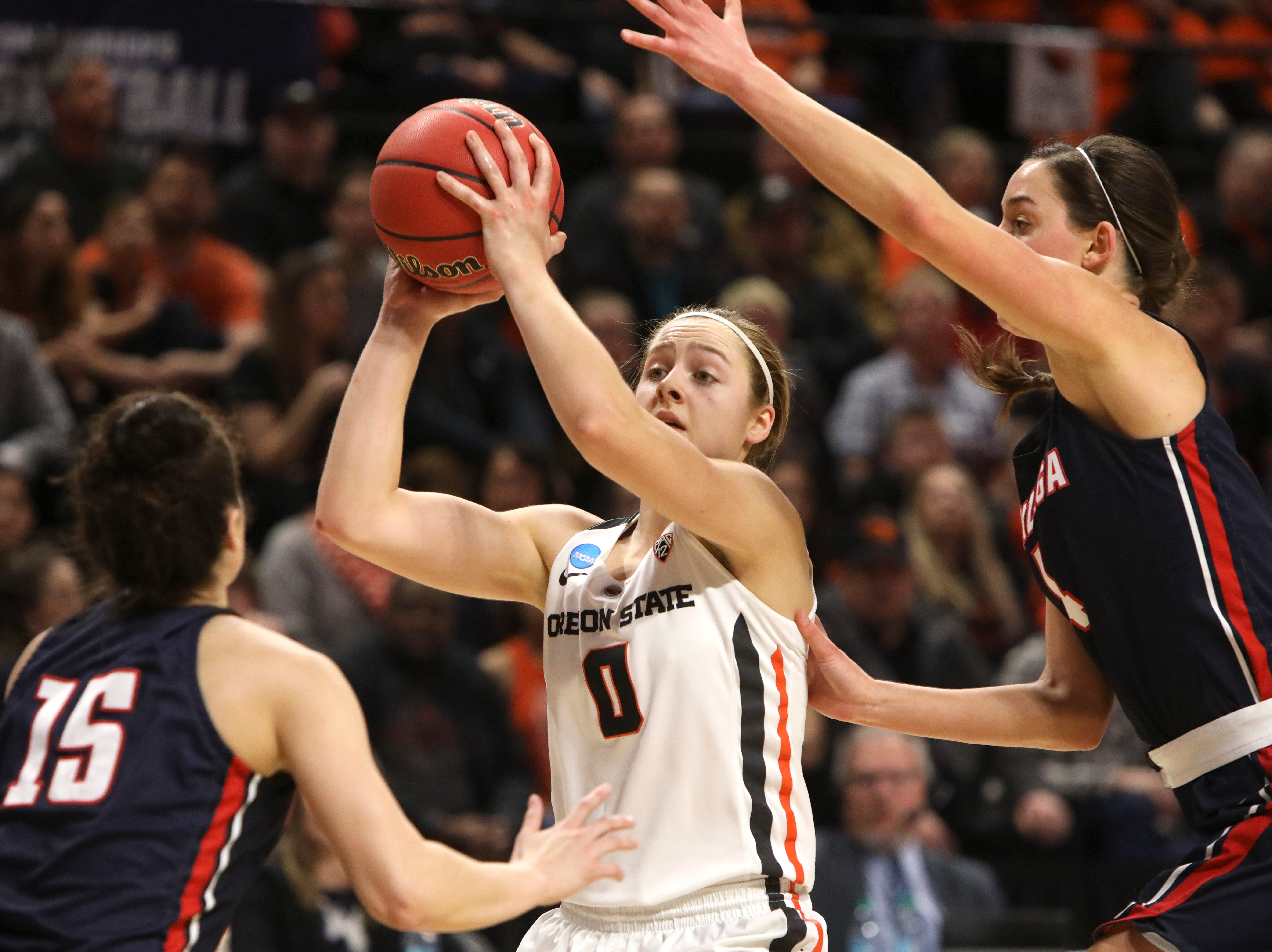 Oregon State's Mikayla Pivec (0) looks for a way through Gonzaga's Jessie Loera (15) and LeeAnne Wirth (4) during the first half of a second-round game of the NCAA women's college basketball tournament in Corvallis, Ore., Monday, March 25, 2019. (AP Photo/Amanda Loman)