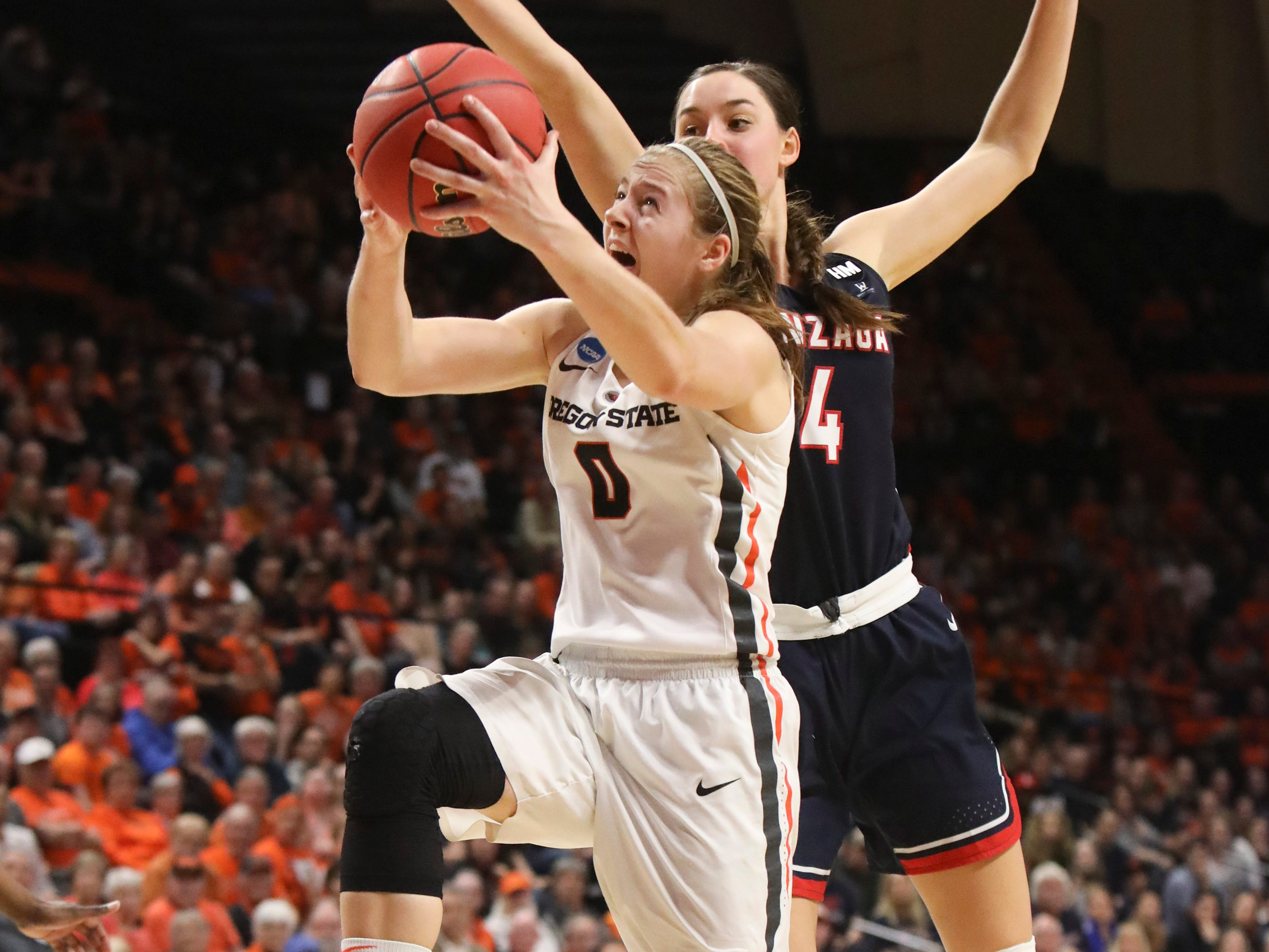 Oregon State's Mikayla Pivec (0) drives to the basket despite in front of Gonzaga's LeeAnne Wirth (4) during the second half of a second-round game of the NCAA women's college basketball tournament in Corvallis, Ore., Monday, March 25, 2019. Oregon State won 76-70. (AP Photo/Amanda Loman)