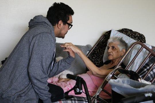 Paul Joseph, nieto de Gloria a quien ella adoptó, sostiene la mano de su abuela.
