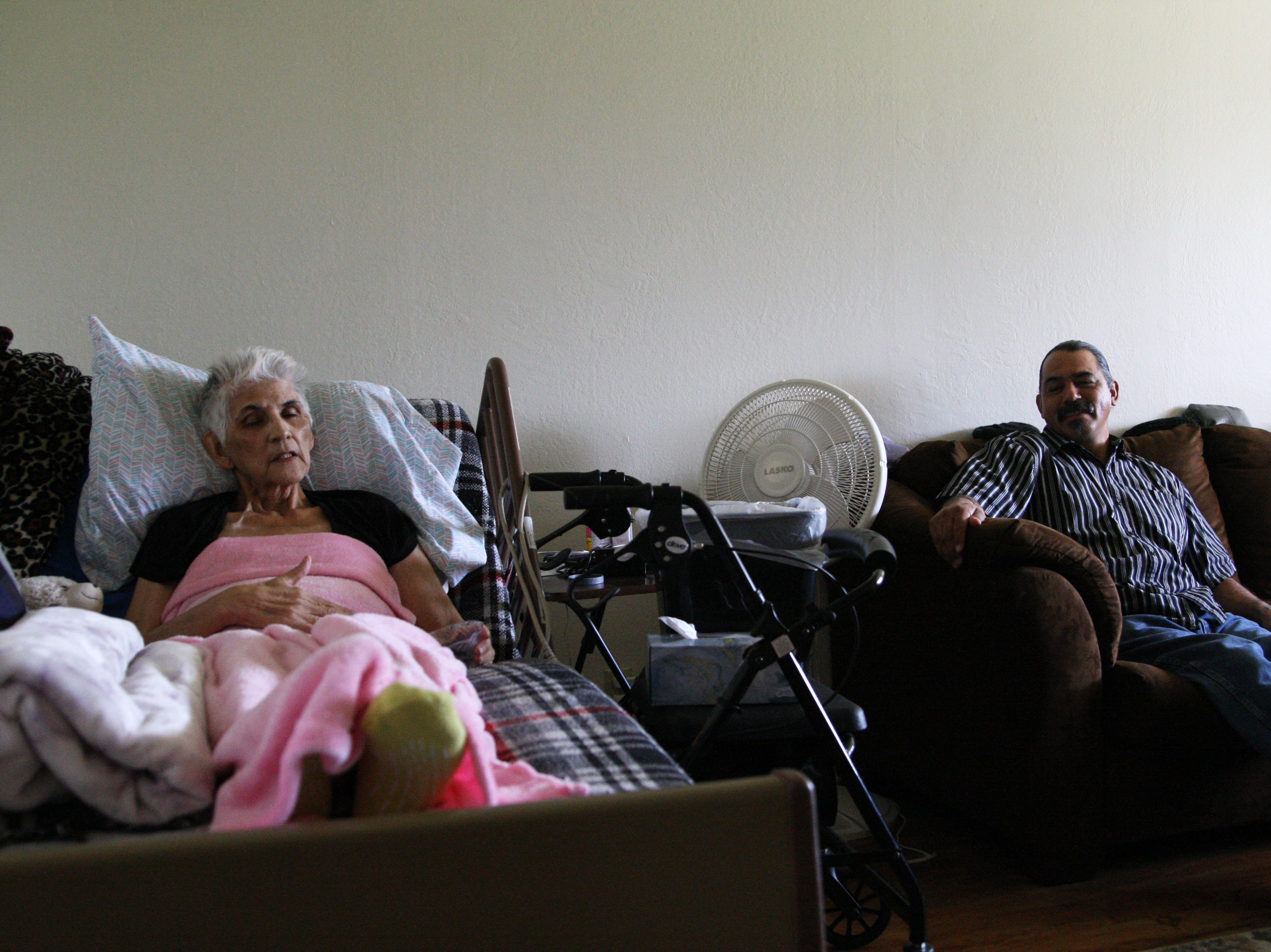 Gloria Torrez rests in her hospital bed in her Salinas home. Her only surviving son, Paul Jr., sits nearby.