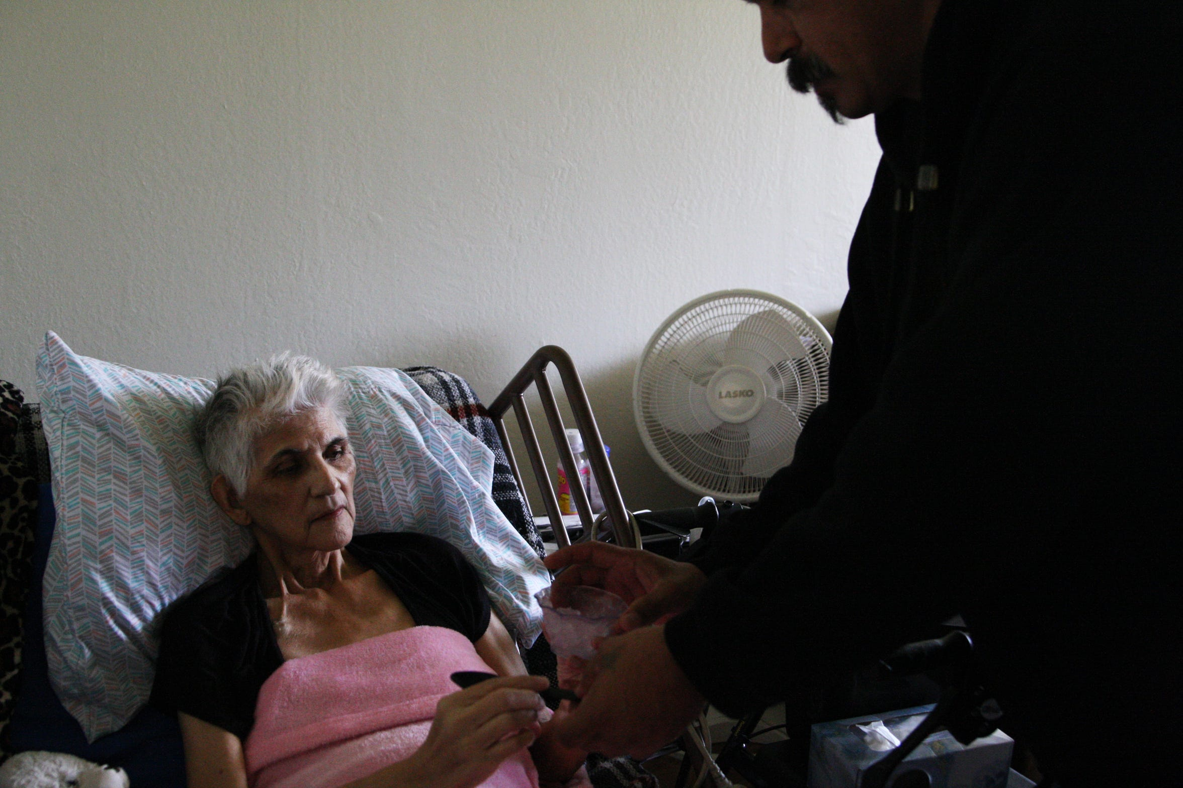 Paul Jr. hands his mother, Gloria Torrez, a freshly re-crushed cup of ice. She can no longer drink water and instead must chew on ice.