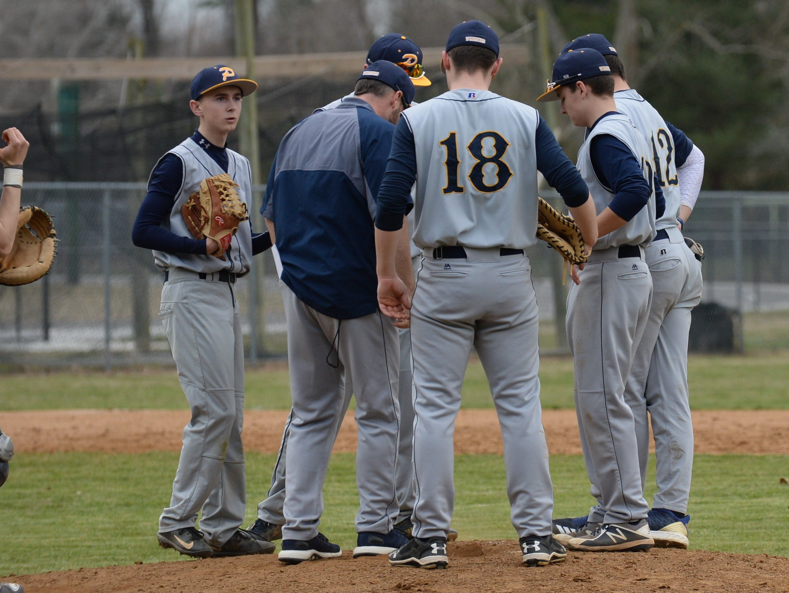 The Pocomoke infield meets at the mound against Mardela on Monday, March 25, 2019.