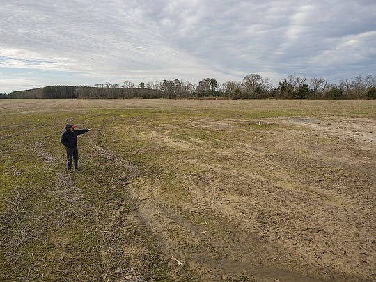 Somerset County farmer Bob Fitzgerald points to a bowl-shaped, 2-acre void created by saltwater intrusion.
