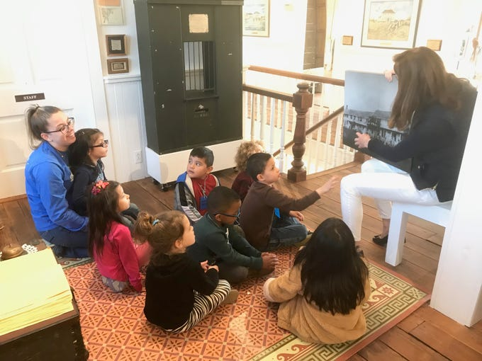 Sally Dickinson, Barrier Islands Center education director, points to a photograph of the Cobb's Island Hotel during a My First Field Trip event with Occohannock Elementary School pre-kindergarten students and teacher Kelsey Misner on Tuesday, March 26, 3019 in Machipongo, Virginia.