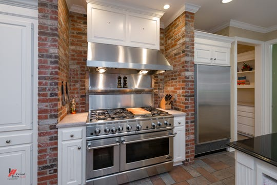 Kitchen appliances include a commercial grade oven with warming lamps and vent hood.