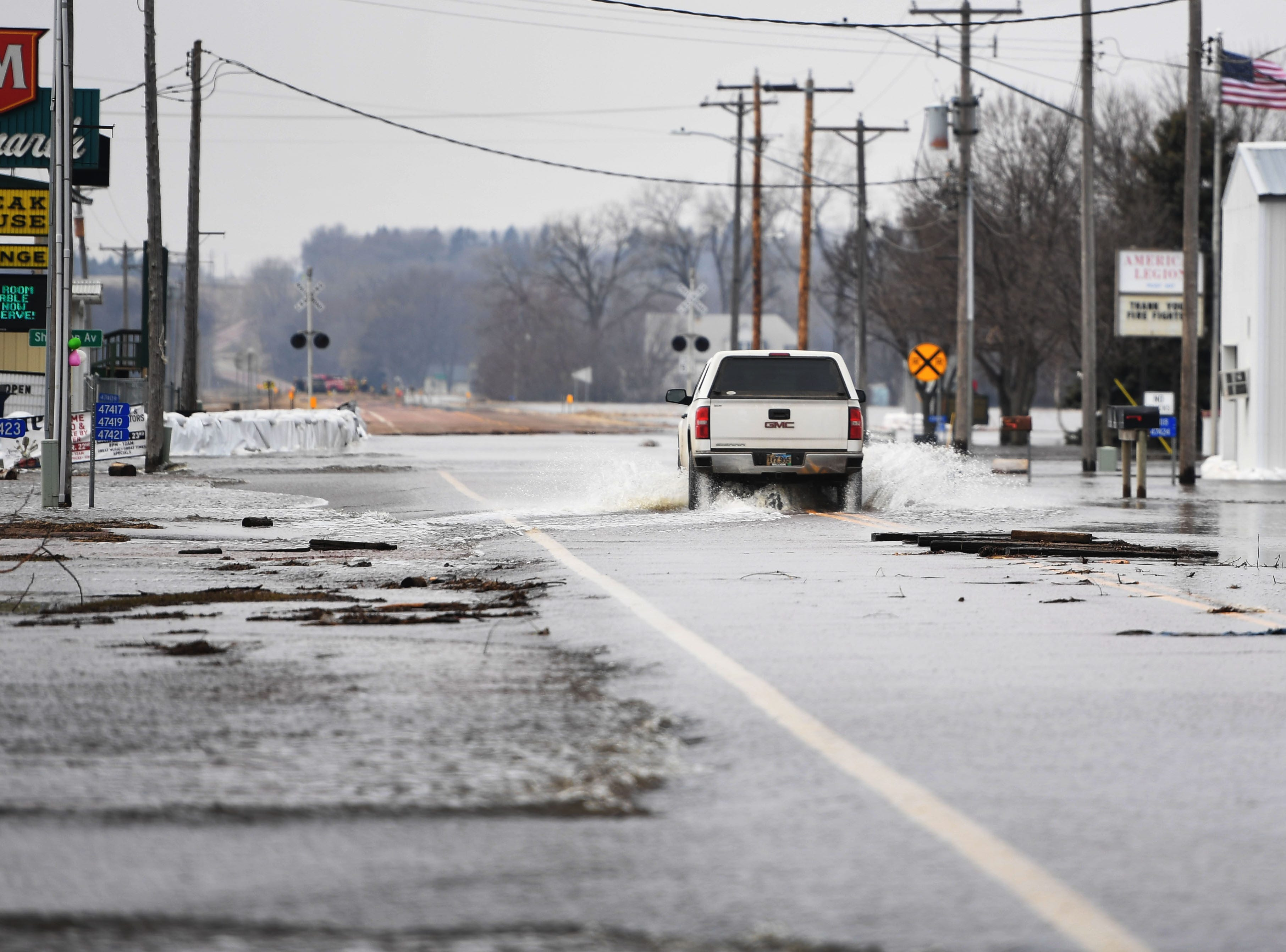 A car drives through 258th street in Renner Tuesday, March 26, in Renner, S.D. The latest river forecasts have the Big Sioux at Dell Rapids staying at 'major' flood level until early next week.