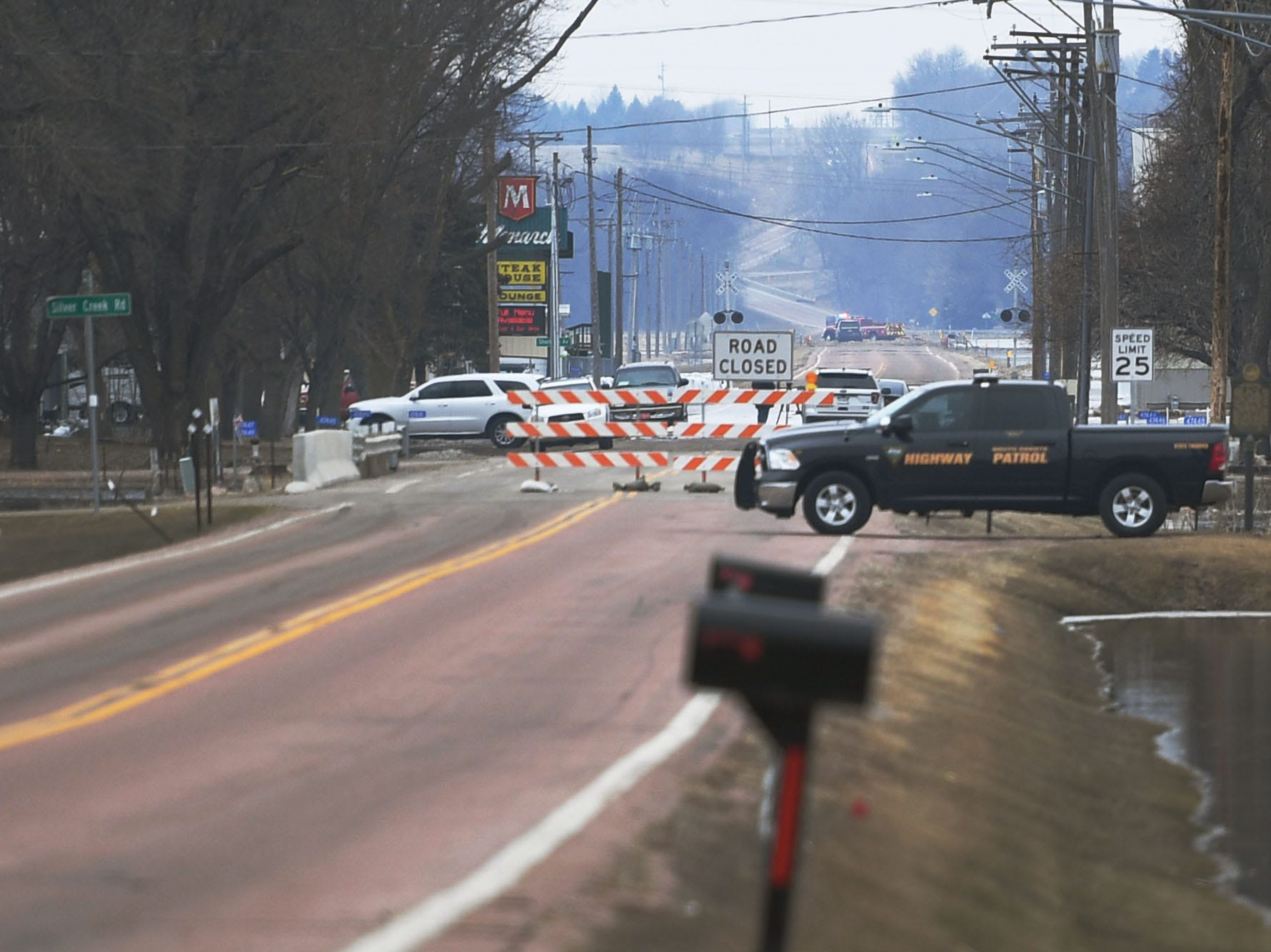 Highway patrol blocks off 258th street for an emergency water rescue in Renner Tuesday, March 26, in Renner, S.D. Two adults, two children, three dogs and three cats were rescued by boat near Ditch Road and Mapleton Road.