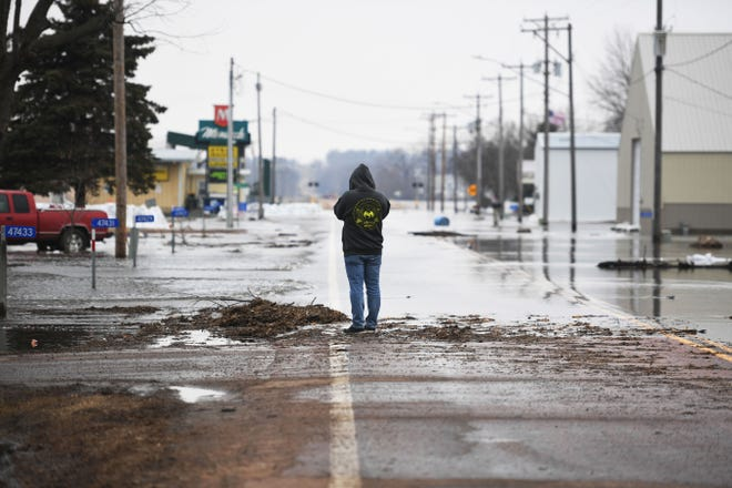 Dustin Griffin takes photos of flooded streets in Renner Tuesday, March 26, in Renner, S.D.