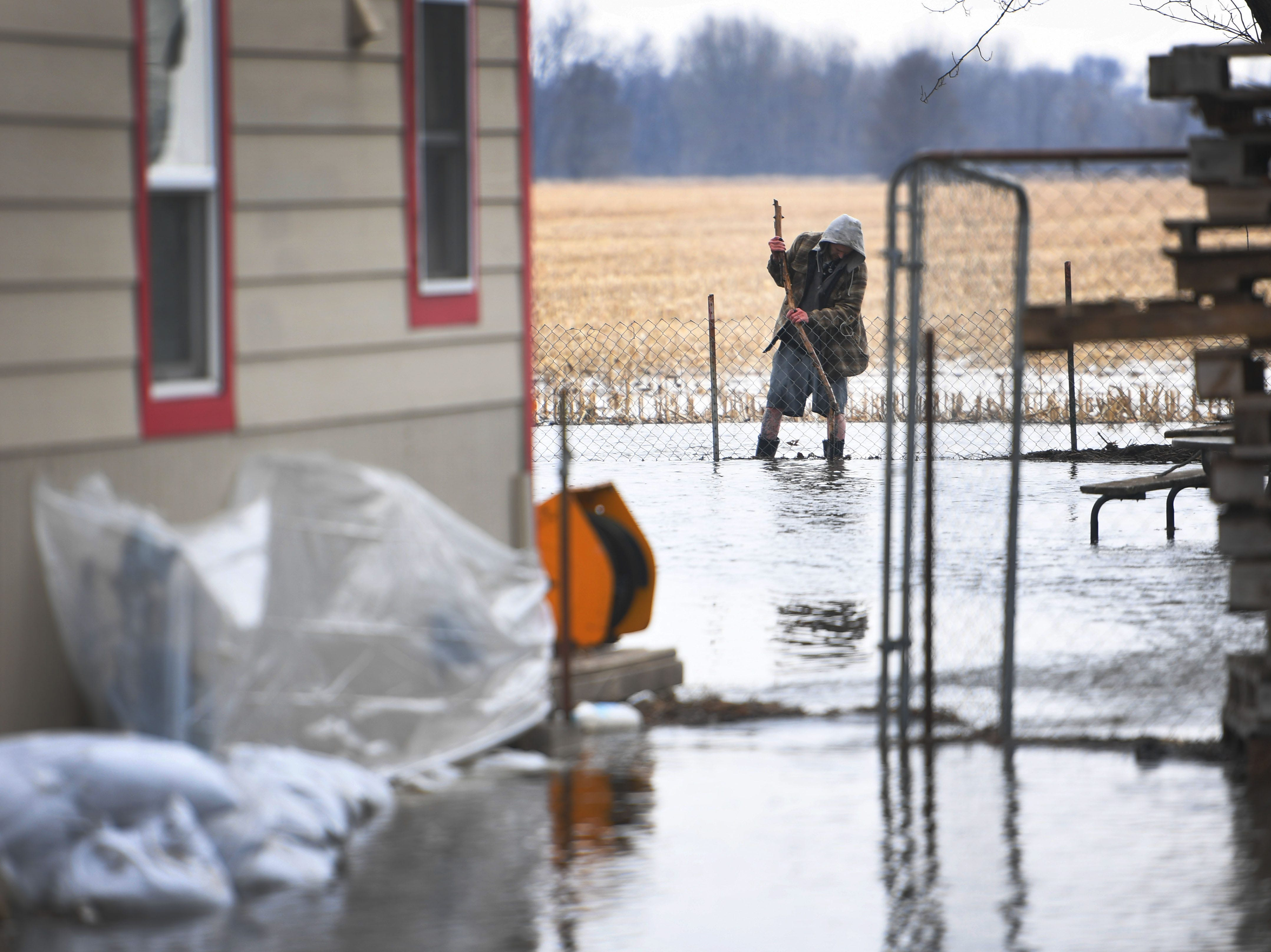A man fixes the fencing in his backyard on 258th street as flooding continues in Renner Tuesday, March 26, in Renner, S.D. The latest river forecasts have the Big Sioux at Dell Rapids staying at 'major' flood level until early next week.