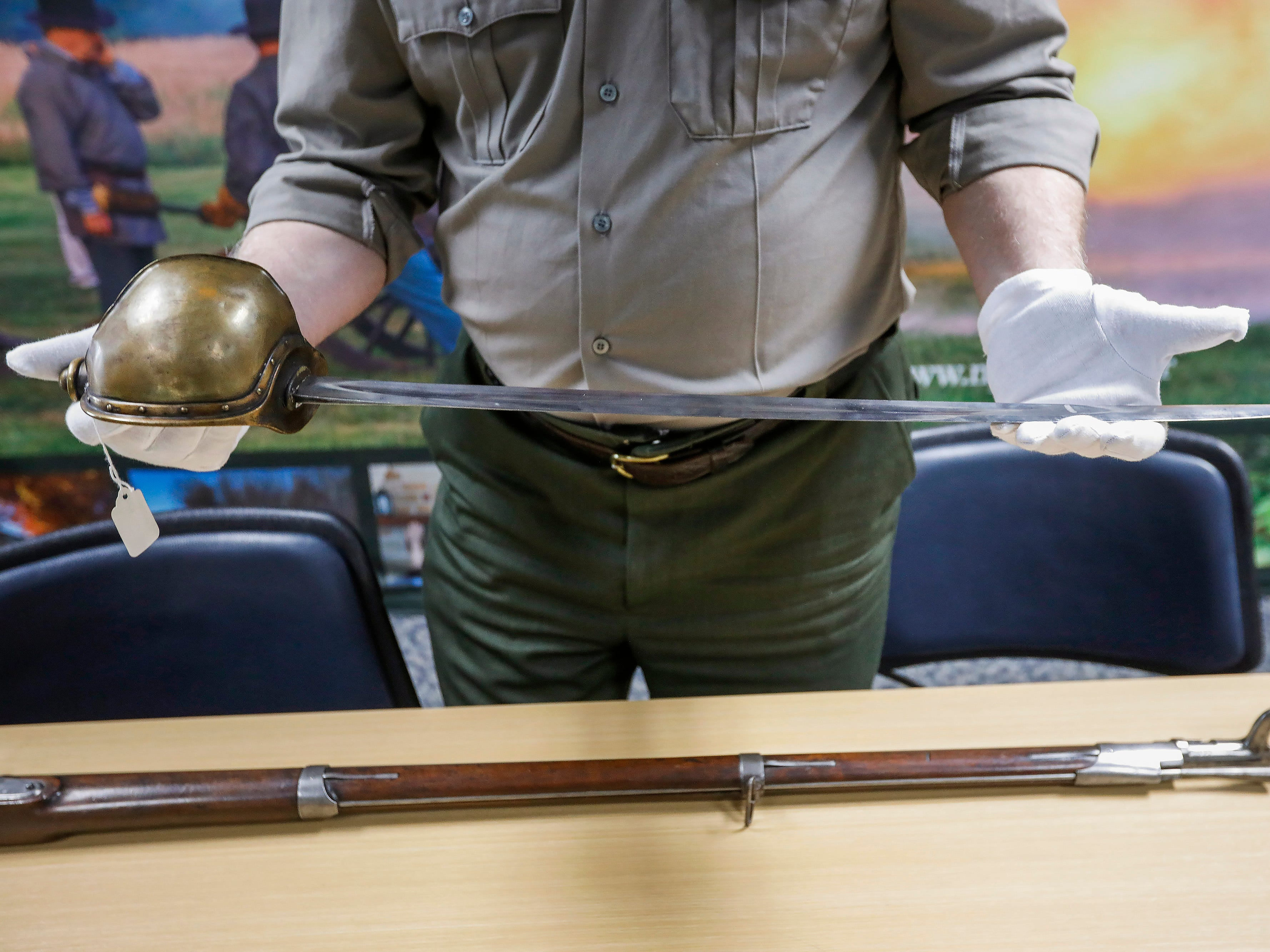 Jeff Patrick, the curator at Wilson's Creek National Battlefield, holds a Civil War navy cutlass. The cutlass is one of the artifacts that will be on display after renovations to the visitors center are completed.