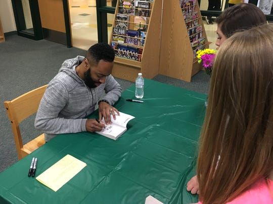 """Matthew Carter, the basis for the main character """"Ghost,"""" autographs the book for students at Wilson Middle School last week."""