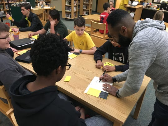 """Matthew Carter, the basis for the main character """"Ghost,"""" autographs the book for students at Wilson Middle School last week before talking with them about his experience growing up."""