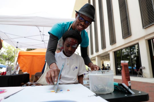 Junior Polo, a teacher with the Prodigy Cultural Arts Program, assists Quatarius Key-Bagley, 9, to create a painted design on a T-shirt during Children's Week at the Capitol.