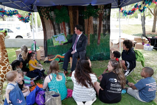 "Mayor John Dailey reads ""Rumble in the Jungle"" to a group during Children's Week at the Capitol, in the courtyard's Storybook Village."