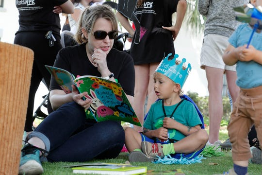 "Early Learning Coalition of the Big Bend family services specialist Kristine Parker reads ""Rumble in the Jungle"" to August Weatherford, 3."