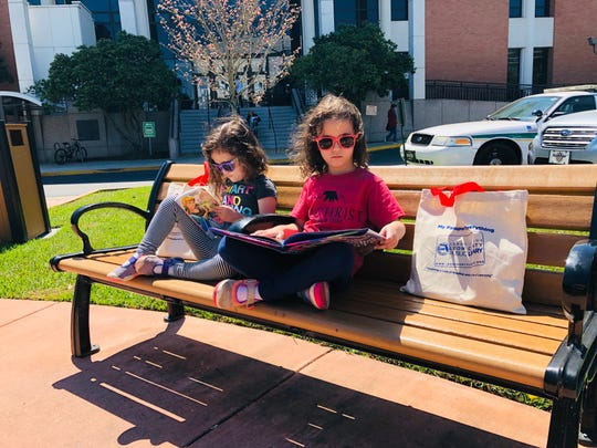 Viv and Apollonia Acevedo can't even wait to get into the car after checking out their latest books from the Leon County Library.
