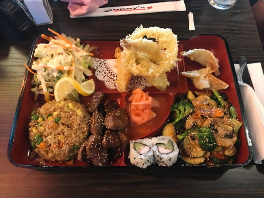 A steak bento lunch box with fried rice, salad, tempura, Japanese dumplings, vegetables and two California sushi rolls from Sunny's in the Northwest.