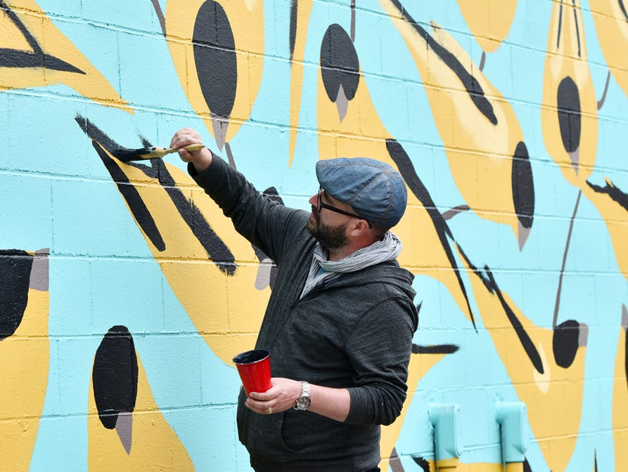 Artist Joseph Bradley paints a mural on the side wall of the Westone building on Stone Ave. in Greenville.