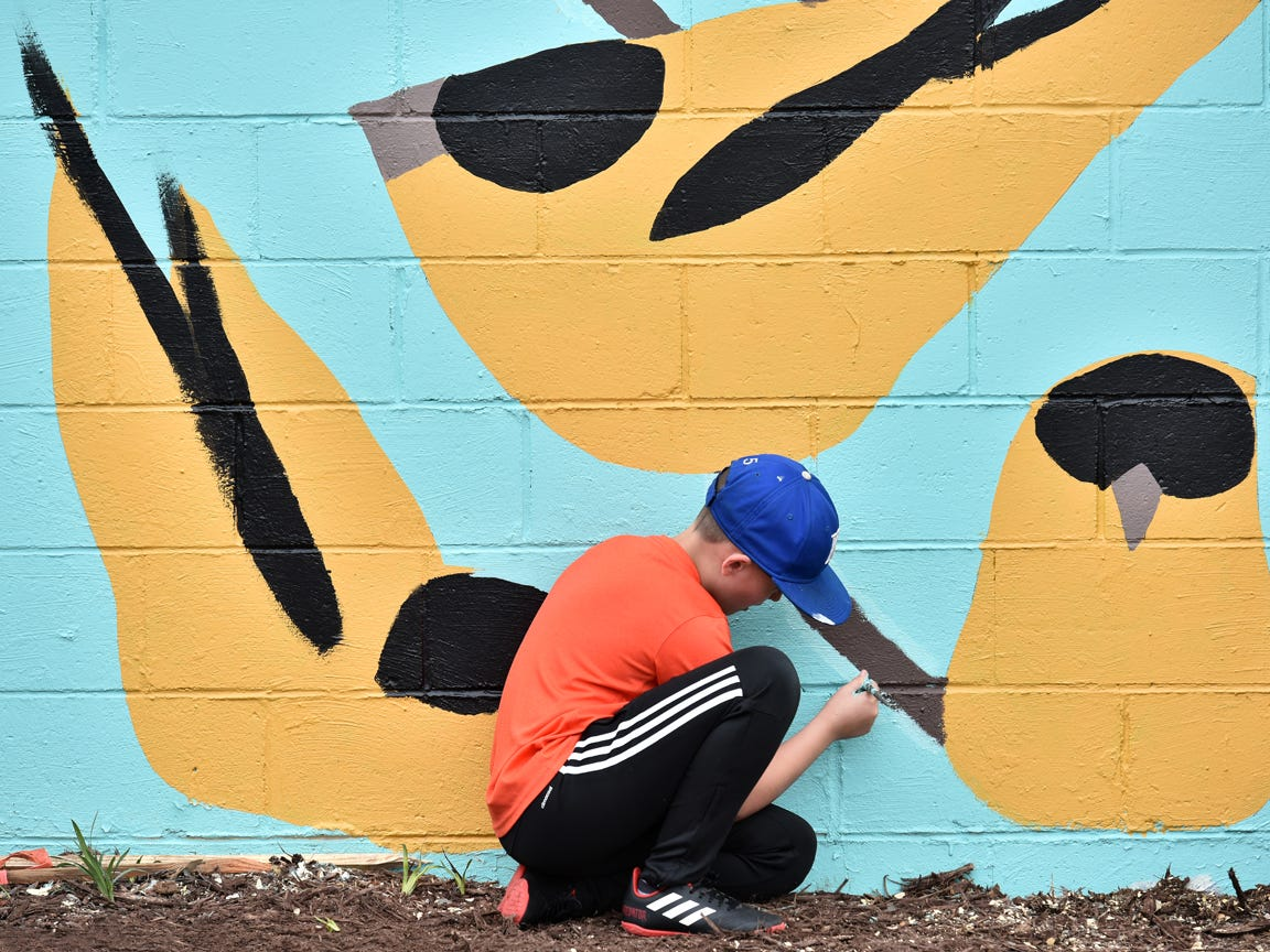Stone Academy fifth-graders and volunteers help paint a mural by local artist Joseph Bradley on the side wall of the Westone building on Stone Ave in Greenville on Tuesday afternoon, March 26, 2019.