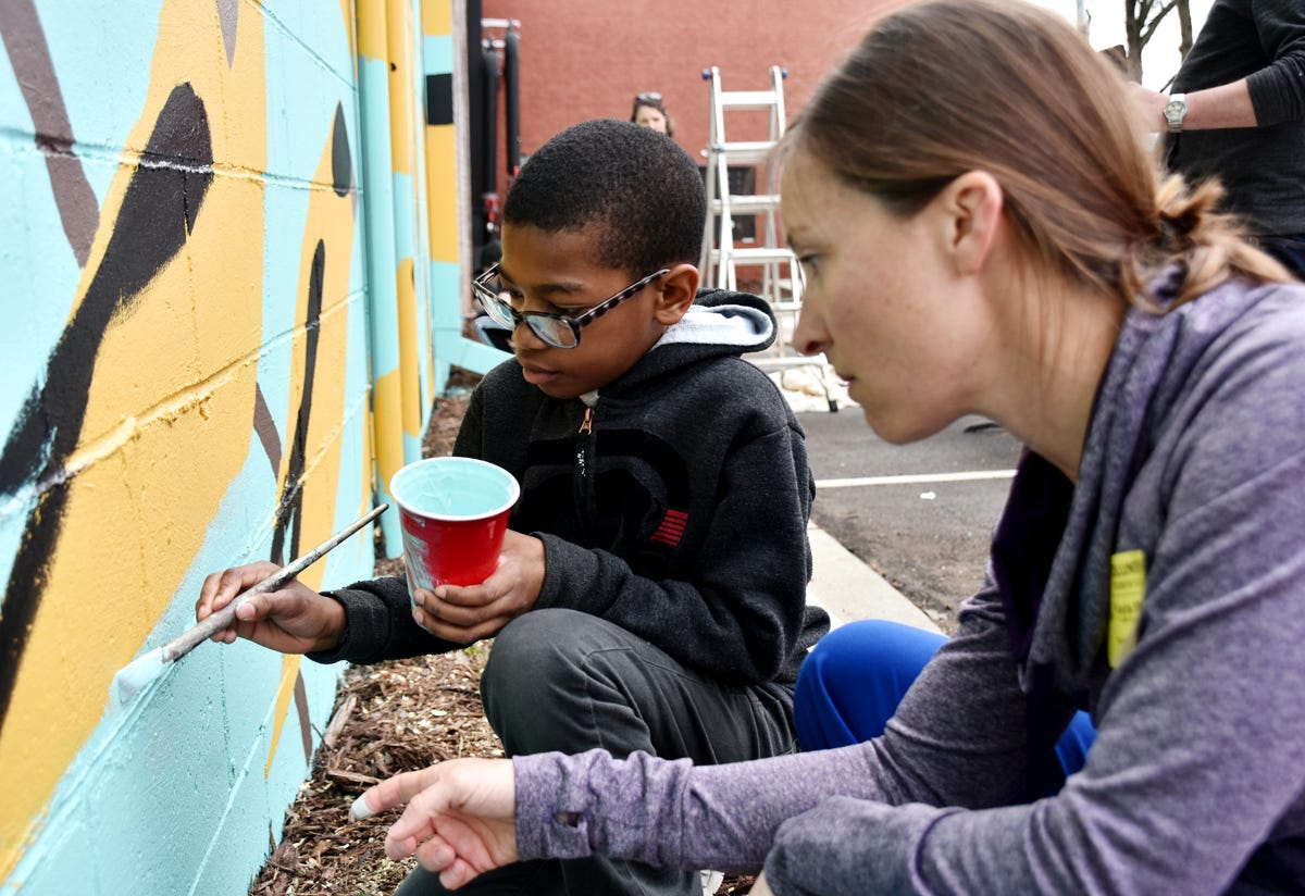 Stone Academy fifth-graders and volunteers help paint a mural by local artist Joseph Bradley on the side wall of the Westone building on Stone Ave in Greenville on Tuesday afternoon, March 26, 2019. The 88 feet wide and 20 feet high mural is part of the Stone Mural Project. Over the last six years, about 750 fifth-graders from Stone Academy have helped paint the project's murals on Stone Ave.