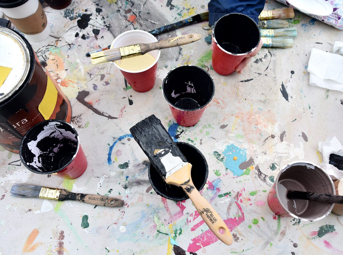 Cups of paint and brushes sit on a table outside of the Westone building where a mural is being painted by artist Joseph Bradley and fifth-graders at Stone Academy.