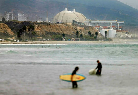 In this June 7, 2013, file photo, surfers stand in water in front of the shuttered San Onofre Nuclear Generating Station. The Nuclear Regulatory Commission is fining Southern California Edison $116,000 for violations in its handling of nuclear canisters at the facility.