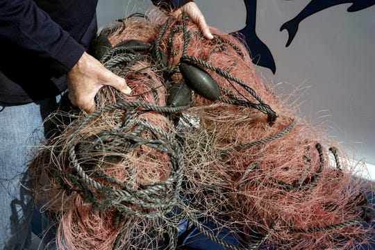 In this Nov. 30, 2015, file photo, Capt. David Anderson of Captain Dave's Dolphin and Whale Watching Safari in Dana Point, shows a net that a whale was found entangled in.