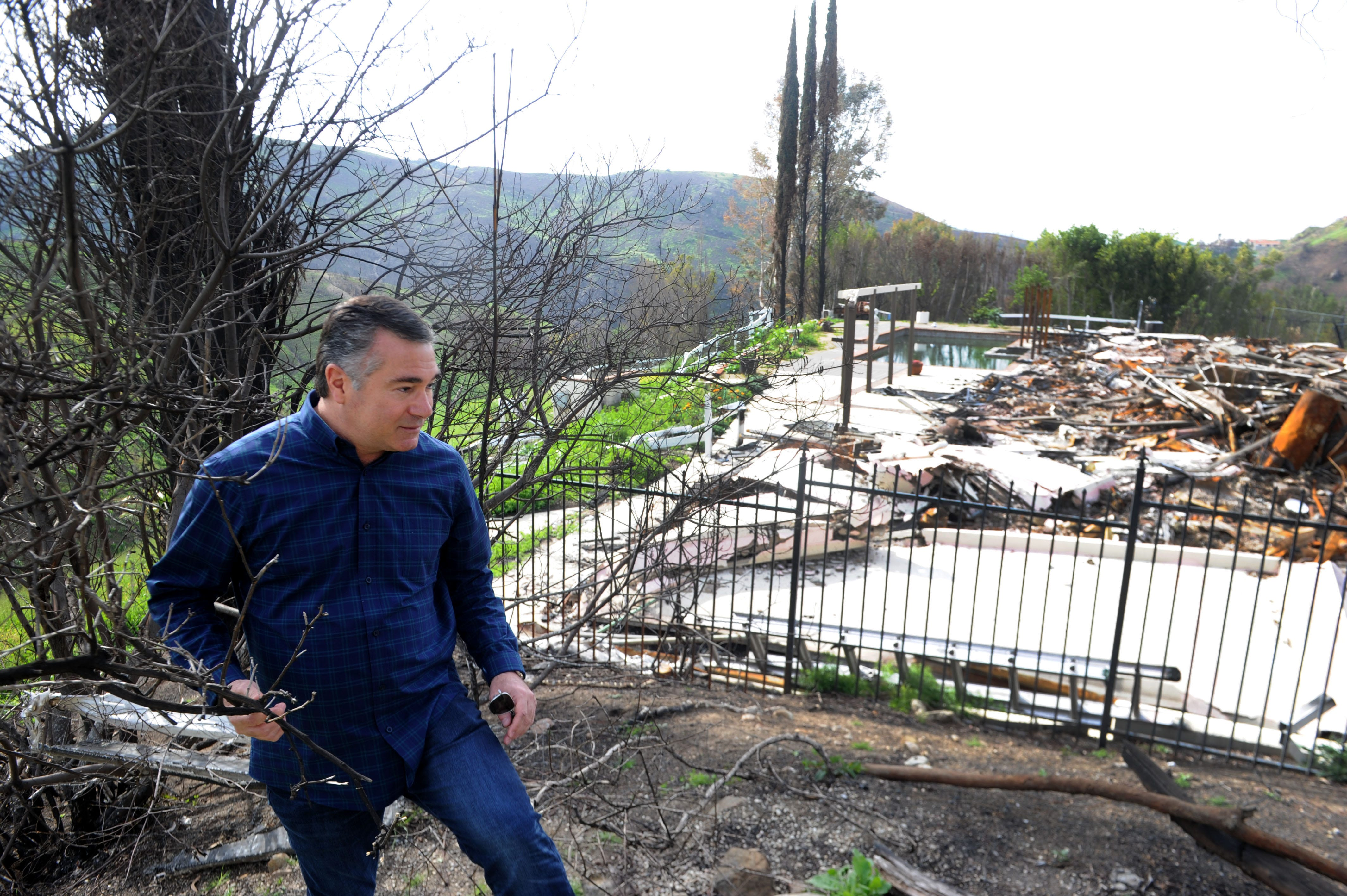 Greg Meneshian walks on the side of his Bell Canyon property. His house and neighbor's house were destroyed by the Woolsey fire in November 2018. The gated community has only one way in and one way out.