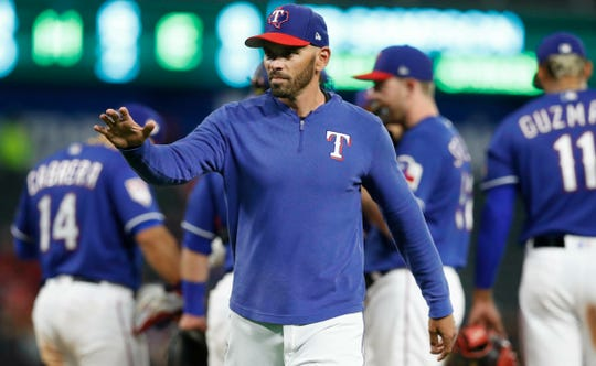 Texas Rangers manager Chris Woodward waves as the walks off the field during the fourth inning of the team's exhibition baseball game against the Cleveland Indians in Arlington, Texas, Monday, March 25, 2019. (AP Photo/LM Otero)