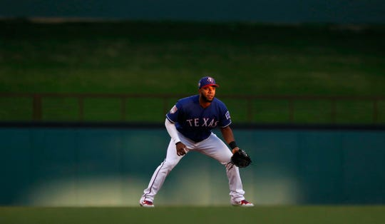 Texas Rangers shortstop Elvis Andrus stand ready in light from the setting sun during the first inning of the team's exhibition baseball game against the Cleveland Indians in Arlington, Texas, Monday, March 25, 2019. (AP Photo/LM Otero)