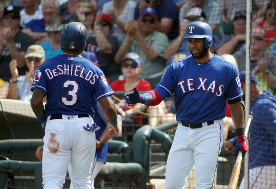 Texas Rangers' Delino DeShields (3) is congratulated by Elvis Andrus after scoring against the Cincinnati Reds during the third inning of a spring training baseball game Wednesday, March 20, 2019, in Surprise, Ariz. (AP Photo/Ross D. Franklin)
