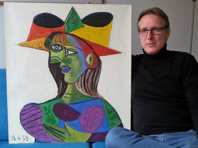 """This image released on Tuesday March 26, 2019 by Arthur Brand, shows Dutch art detective Arthur Brand with """"Buste de Femme"""", a recovered Picasso painting."""